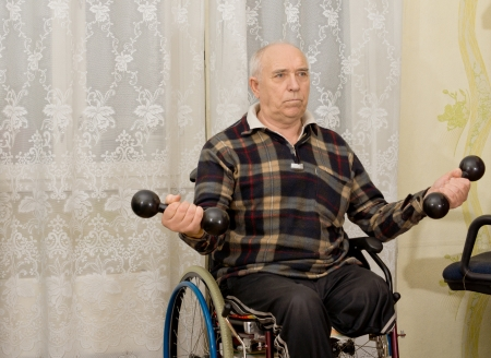 Senior handicapped male amputee sitting in his wheelchair doing exercises working out with a pair of dumbbells photo