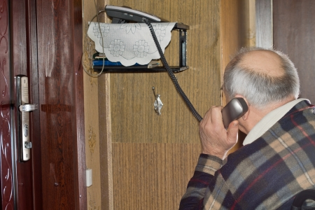 Elderly man talking on a telephone sitting with his back to the camera holding the handset to his ear photo