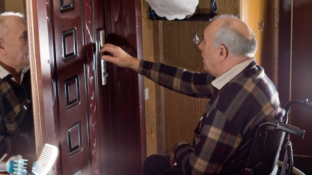 Elderly disabled man in a wheelchair checking the locks on the front door of the house to ensure he is safe and secure Stock Photo