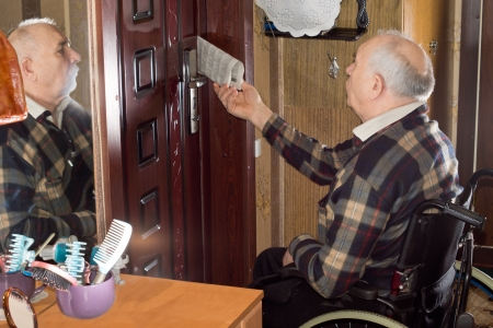 Disabled elderly man in a wheelchair collecting his newspaper which has been posted through his door with him reflected in the mirror alongside photo