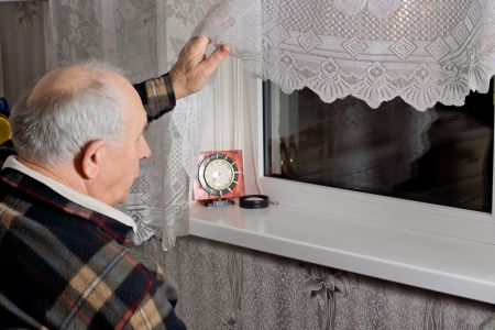 Elderly man peering out through the window into the dark night as he waits for an expected arrival with a clock in front of him on the window sill Stock Photo