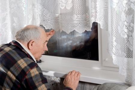 Hombre mayor mirando a trav�s de una ventana en la noche mientras observa a alguien para llegar Foto de archivo