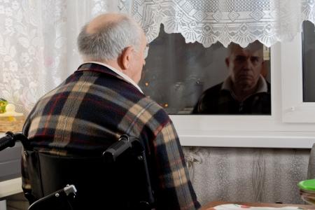 暗い夜にガラスを通して見つめるカメラに背を向けてウィンドウで待っている車椅子シーティングで老人 写真素材