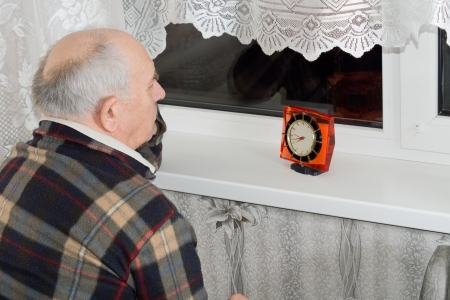 Senior man sitting waiting in front of a window at night with a clock in front of him as he counts down the time to an expected arrival photo