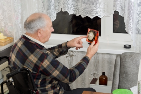 Elderly man in a wheelchair checking the clock as he sits in front of a window at night waiting for somebody to arrive photo