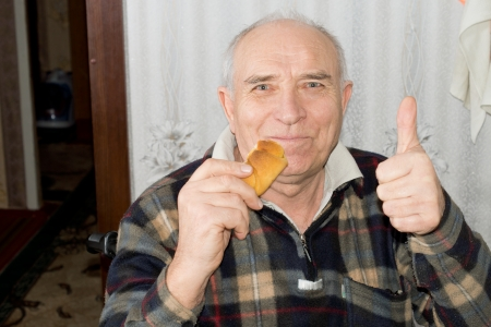 Smiling senior man giving a thumbs up gesture of approval as he munches on a fresh roll in his house