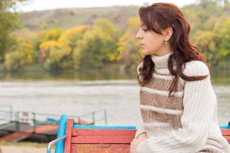 meditative: Pensive attractive young woman sitting outdoors in autumn on a rustic wooden bench above a lake or river turned in profile looking into the frame and copyspace