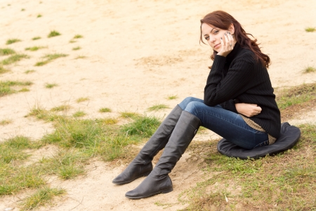 downhearted: Wistful young woman sitting outdoors alone on a cushion on sandy ground looking at the ground with a sombre expression as she rests her chin on her hand Stock Photo