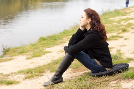 Lonely young woman sitting on a cushion on the ground on the shore above a tranquil lake daydreaming as she stares out over the calm water