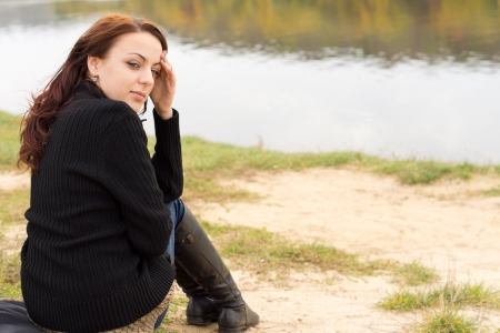 tranquillity: Beautiful woman enjoying the tranquillity of the outdoors sitting above calm water with autumn reflections looking back over her shoulder at the camera