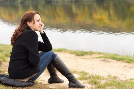 sitting on the ground: Trendy young woman in boots and jeans with long brunette hair sitting on a river bank overlooking tranquil water with autumn reflections