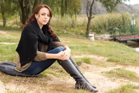 cradling: Thoughtful lonely young woman in trendy boots and jeans sitting on a cushion on the ground in a park cradling her knees in her arms as she stares at the camera