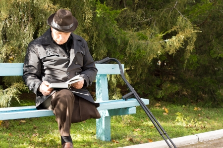 Elderly handicapped man on crutches with only one leg having suffered an amputation sitting in the sun reading his book on a park bench in a warm coat and hat photo