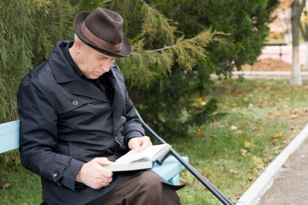 Disabled retired man on crutches reading in the park sitting on a wooden bench in a warm overcoat and hat with his crutches alongside him photo