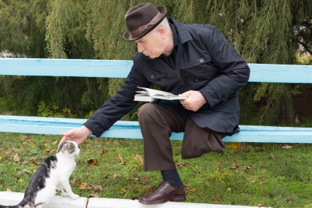 amputated: Elderly disabled man with one leg amputated sitting on a park bench with his book reaching down and stroking a cat