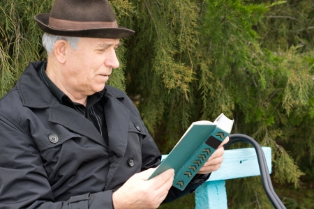 Senior gentleman relaxing reading his book outdoors sitting on a garden bench against greenery with a contented smile on his face photo