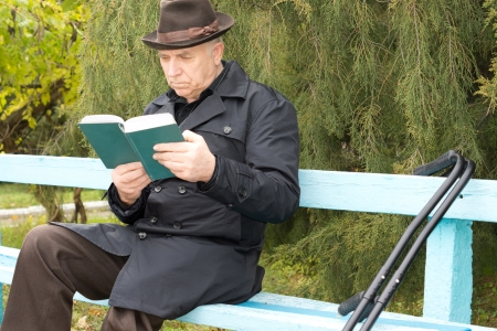 Disabled man on crutches sitting reading in the sun on a rustic wooden bench in the park in his warm overcoat and hat as he enjoys the last sunshine of the autumn photo