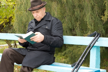 Elderly disabled gentleman sitting outdoors reading in a hat and warm coat on a wooden park bench with his crutches alongside him photo