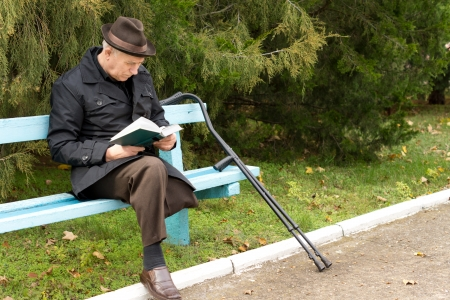 Senior amputee enjoying his book in the sunshine sitting on a park bench with his crutches alongside him in a hat and warm coat photo
