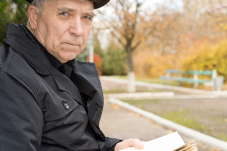 Close up portrait of an elderly man in an overcoat and hat sitting outdoors in the autumn sunshine in a park enjoying the peace while reading his book looking at the camera with a serious expression photo
