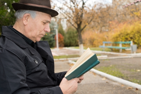 Close up side view portrait of an elderly gentleman in an overcoat and hat reading his book outdoors in the autumn sun and enjoying the peace of the public park photo