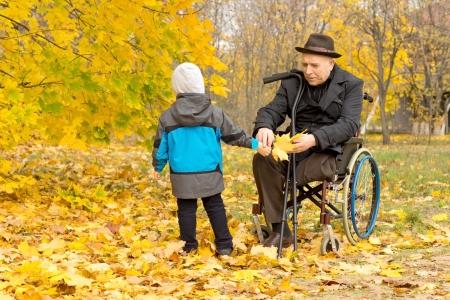 色鮮やかな紅葉の中で遊んで車椅子に限られている障害祖父を持った少年の美しい森林の葉します。