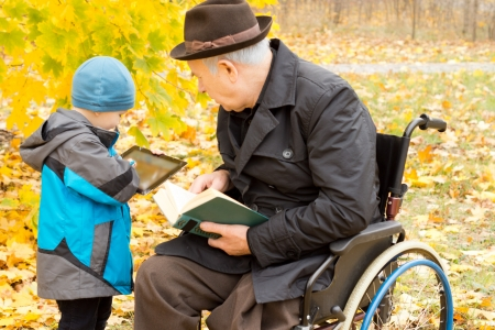 Young boy showing his grandfather something on his tablet computer as the old man sits in a wheelchair in his overcoat and hat enjoying a book in a colourful autumn garden photo