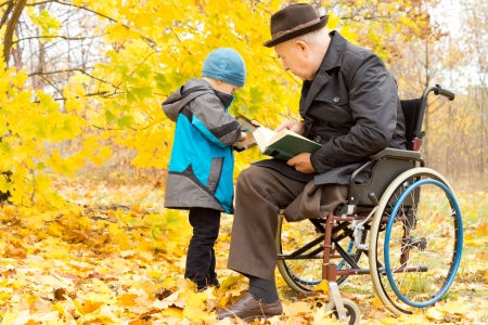 Young child with his disabled grandfather, who has one leg amputated and is sitting in a wheelchair, sharing information on his tablet computer as they enjoy a day in the fresh air in an autumn park photo
