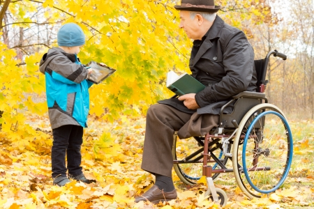 Handicapped elder man with one leg amputated sitting in a warm overcoat and hat in his wheelchair in a colourful autumn park watching his grandson play on his tablet computer photo
