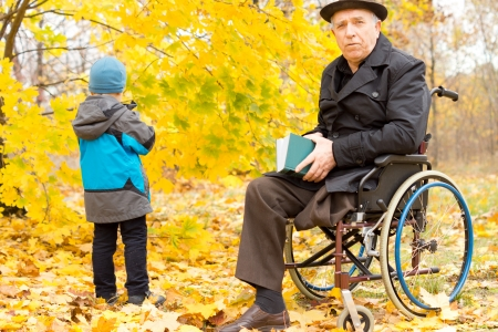amputated: Handicapped senior man with one leg amputated accompanying a young child on a day out in a colourful yellow autumn park sitting in his wheelchair with a book Stock Photo