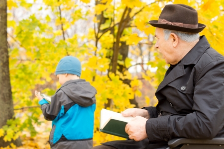 Grandfather in a warm overcoat and hat sitting with a book watching over his young grandchild in a colourful yellow autumn garden photo