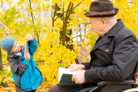 Young boy with his grandfather, who is sitting in a wheelchair, playing with his tablet computer watched over by the old man in an autumn forest photo