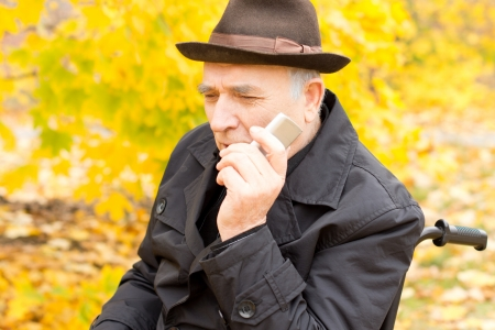 Senior man holding a mobile phone to his cheek with a concerned thoughtful expression after hearing news from a friend or family member as he enjoys nature in a colourful fall garden photo