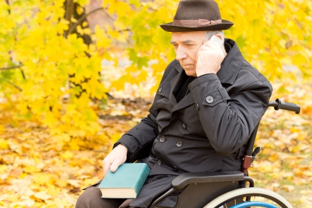 Thoughtful handicapped elderly man sitting in his wheelchair outdoors in a colourful yellow fall forest with his mobile phone resting against his cheek as he thinks over his recent conversation photo