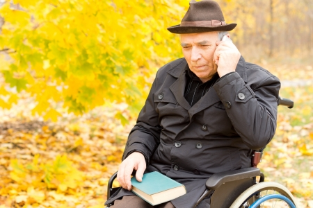 perturbed: Elderly disabled man sitting in his wheelchair in a colourful autumn park using a mobile phone listening intently to the conversation Stock Photo
