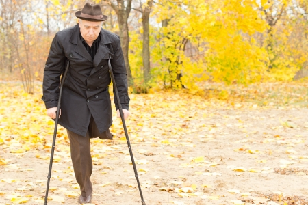 amputated: Elderly disabled gentleman with one leg amputated walking on crutches in an autumn park with colourful yellow foliage