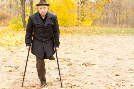 Lonely one-legged senior Caucasian man walking with crutches in an Autumn day in the park, with withered foliage in the background photo