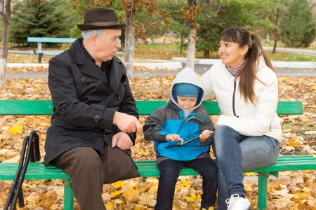 Disabled elderly man with one leg amputated sitting on a wooden park bench outdoors playing with his daughter and grandson who is browsing the internet on a tablet-pc photo