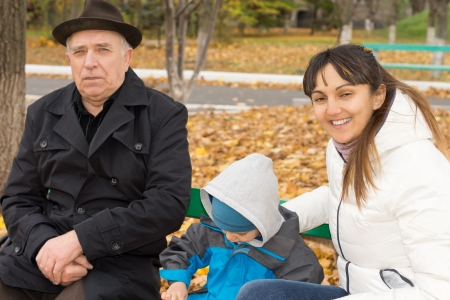 Smiling friendly woman sitting on a wooden park bench with her young son and elderly father as they enjoy an invigorating autumn day in the fresh air photo