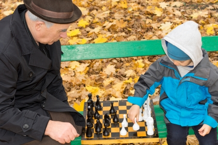 Elderly grandfather sitting on a wooden park bench outdoors in autumn teaching his cute little grandson to play chess photo