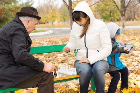 Attractive woman sitting on a park bench in the cold autumn weather playing chess with an elderly man while her young son amuses himself on a tablet computer behind her photo