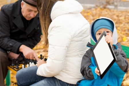 Young boy bundled up in warm clothing against the cold autumn weather sitting on a park bench playing with a tablet computer while his mother and grandfather play chess alongside him photo