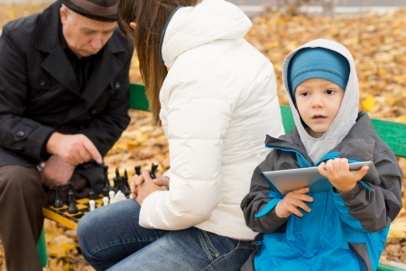 Cute young boy dressed in warm clothing against the chilly autumn weather sitting on a park bench holding a tablet computer while his mother and grandfather play chess alongside him photo