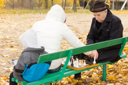 Grandfather playing chess with his daughter as they sit together in the chilly weather on a park bench with a young grandchild accompanying them photo
