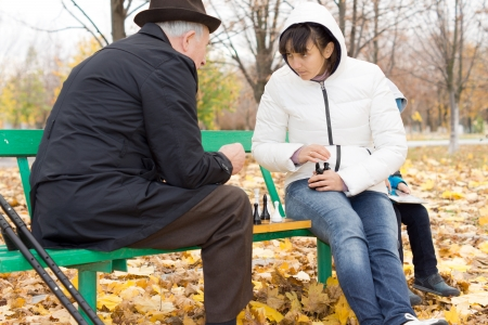 Two friends playing chess in the park with an elderly man in an overcoat and younger woman sitting on a bench with the chessboard between them photo