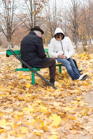 Disabled elderly man with crutches and an attractive younger woman playing chess sitting together on a wooden park bench wrapped up warmly against the cold autumn weather photo