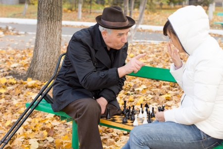 Elderly man arguing during a game of chess shaking a finger at a younger woman as the two sit together on a wooden park bench surrounded by fallen autumn leaves photo