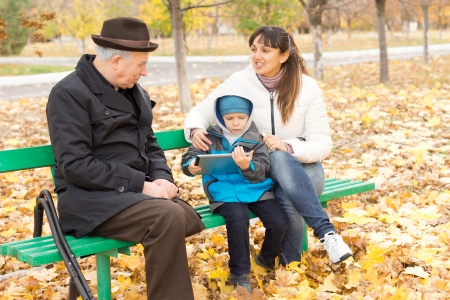 Three generations - a disabled grandfather on crutches, an attractive smiling mother and her cute young son who is playing on a tablet-pc, all sitting together on a wooden park bench in autumn photo