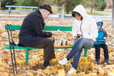 Attractive woman playing chess with her father as they sit together outdoors on a park bench with the chessboard between them as a her young son plays on a tablet-pc alongside photo
