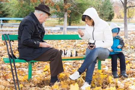 Three generations of a family playing chess with an elderly man and his daughter sitting on a park bench with the chessboard between them as his young grandson amuses himself playing on a tablet-pc photo